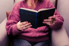 Old woman reading at home Stock Photos