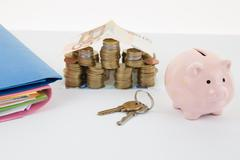 Small House made with money and pink Piggy Bank. keys and documents - stock photo