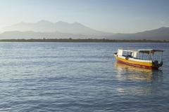 Indonesia, West Nusa Tenggara, Mount Rinjani, Motorboat in sea - stock photo