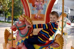 Little boy (6-7) riding carousel horse - stock photo