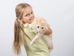 Six year old girl holding a cat in her arms Kuvituskuvat