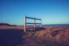 Fence on hill at sunset near the sea - stock photo