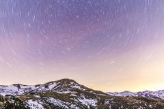 Spain, Catalonia, Gerona, Pyrenees, Star trail above snowcapped mountain range Stock Photos