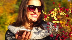 Happy woman holding cellphone and bouquet of brier, steadycam shot, slow motion  Stock Footage