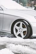 Clesup view of the car tires covered with snow at the cold winter season - stock photo
