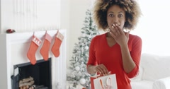 Astonished young woman holding a Christmas gift Stock Footage