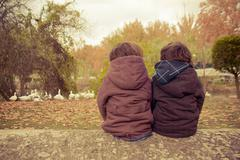 Two boys (2-3) sitting in meadow Stock Photos