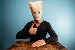 Man with bag over head giving thumbs up - stock photo