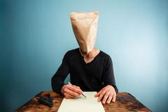 Man with bag over head writing suicide note Stock Photos