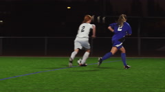 A female soccer player scores a goal during a game at night - stock footage