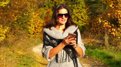 Woman walking on pathway and answering the phone, steadycam shot, slow motion sh Arkistovideo