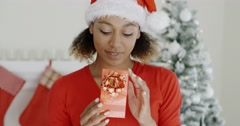 Excited young woman looking at a Christmas gift Stock Footage