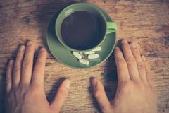 Man having pills and coffee Stock Photos