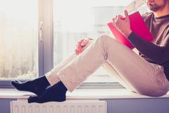 Young man reading on window sill Stock Photos