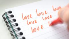 Time lapse of writing word LOVE many times with red marker - stock footage