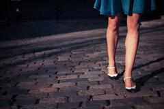 Young woman in skirt walking on a cobbled street - stock photo
