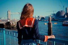 Young woman standing on the bank of the Thames in London Stock Photos