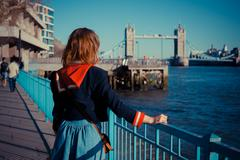 Young woman standing on the bank of the Thames in London - stock photo