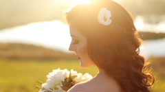 Close-up portrait of a beautiful young sexy girl brunette bride with flower  in Stock Footage