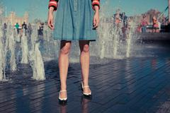 Young woman standing by fountain in city on a hot day Stock Photos