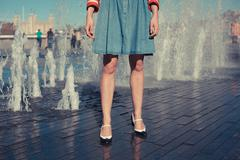 Stock Photo of Young woman standing by fountain in city on a hot day