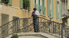 Man standing on a bridge and taking pictures in Campiello San Vidal, Venice Stock Footage