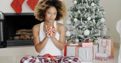 Blissful young woman drinking coffee at Christmas Stock Footage