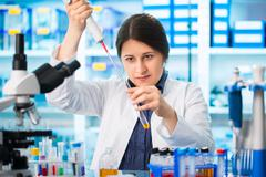 laboratory assistant analyzing a blood sample - stock photo