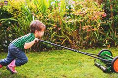 Boy (2-3) mowing lawn - stock photo