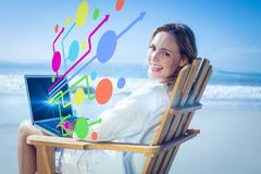 Composite image of gorgeous blonde sitting on deck chair using laptop on beach Stock Photos