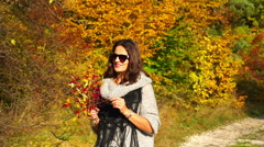 Woman walking with bouquet of briers and smiling, steadycam shot - stock footage