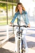 Young happy smiling blonde beautiful woman wearing in white jeans riding bike Stock Photos