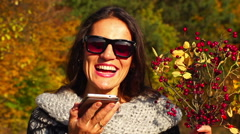 Happy woman talking on cellphone and holding briers, steadycam shot, slow motion Stock Footage
