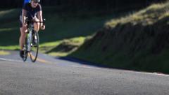 Woman biking uphill, sunny day Stock Footage