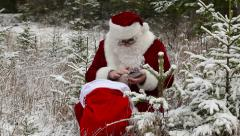 Santa Clause with tablet PC near gift bag in the snowy woods - stock footage