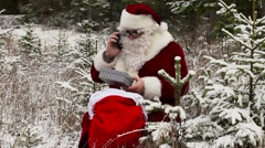 Santa Clause with smartphone near gift bag in the snowy woods - stock footage