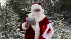 Santa Clause with gift box in the snowy woods - stock footage