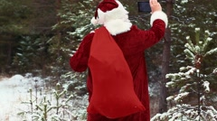 Santa Clause filmed with tablet PC in the snowy woods - stock footage