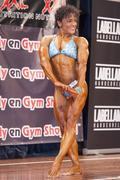 Female bodybuilder in triceps pose and blue bikini Stock Photos
