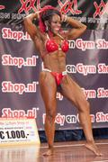 Female bodybuilder in abdominals and thigs pose and red bikini Stock Photos