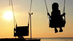 Boy on the swing near the river at dawn jumps from a swing, silhouette Stock Footage