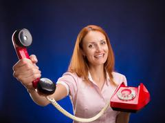 Redhead women with red telephone. Stock Photos