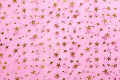 Gold stars on pink textile Stock Photos