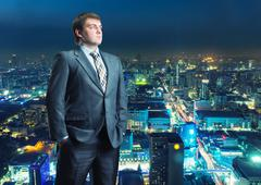 Businessman staying infront of city view - stock photo