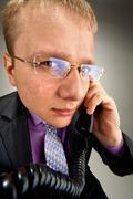 Bizarre businessman talking by phone - stock photo