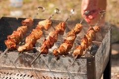 Grilling shish kebabin in brazier Stock Photos