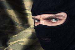 Serious man in a balaclava mask - stock photo