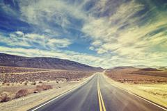 Vintage stylized endless country highway in Death Valley, USA. Stock Photos