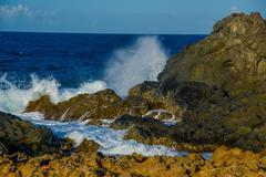 Waves crashing on the rocks of Aruba, ABC caribbean islands Stock Photos