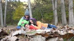 Two female friends takling, chatting,  sitting in autumn forest leaves Stock Footage